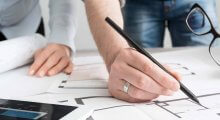 Image of two people working on property plans