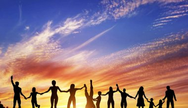 Image of a row of adults and children holding hands against a sunset sky
