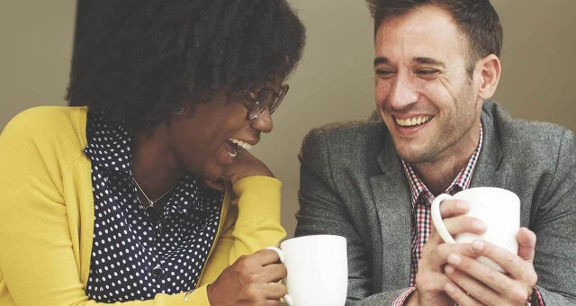 Photo of two people chatting over coffee