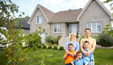Photo of a happy family standing in front of a house