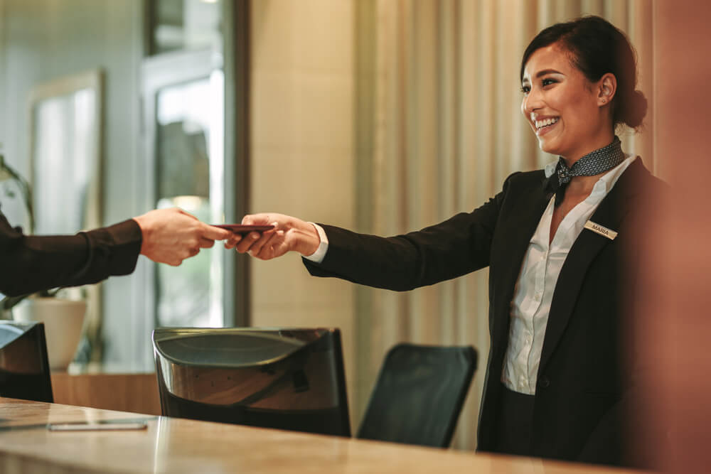 Image of a receptionist handing over a pass to a client